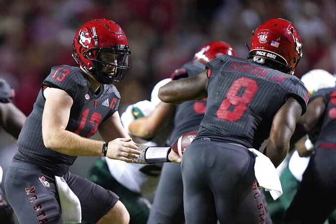 North Carolina State quarterback Devin Leary (13) hands the ball off to running back Ricky Person Jr. (8) during the first half of an NCAA college football game against South Florida in Raleigh, N.C., Thursday, Sept. 2, 2021. (AP Photo/Gerry Broome)