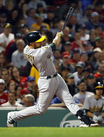 Oakland Athletics' Jonathan Lucroy follows through on a two-run double against the Boston Red Sox during the fourth inning of a baseball game at Fenway Park in Boston Monday, May 14, 2018. (AP Photo/Winslow Townson)