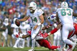 Miami Dolphins quarterback Ryan Fitzpatrick (14) tries to scramble away from Buffalo Bills defensive end Jerry Hughes (55) in the first half of an NFL football game, Sunday, Oct. 20, 2019, in Orchard Park, N.Y. (AP Photo/Adrian Kraus)