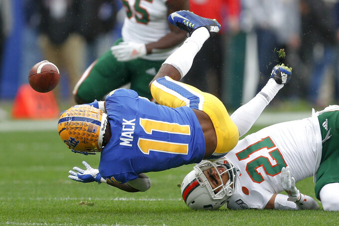 Pittsburgh wide receiver Taysir Mack (11) fumbles the ball after getting hit by Miami place kicker Bubba Bolden (21) during the first half of an NCAA college football game, Saturday, Oct. 26, 2019, in Pittsburgh. Miami recovered the ball. (AP Photo/Keith Srakocic)