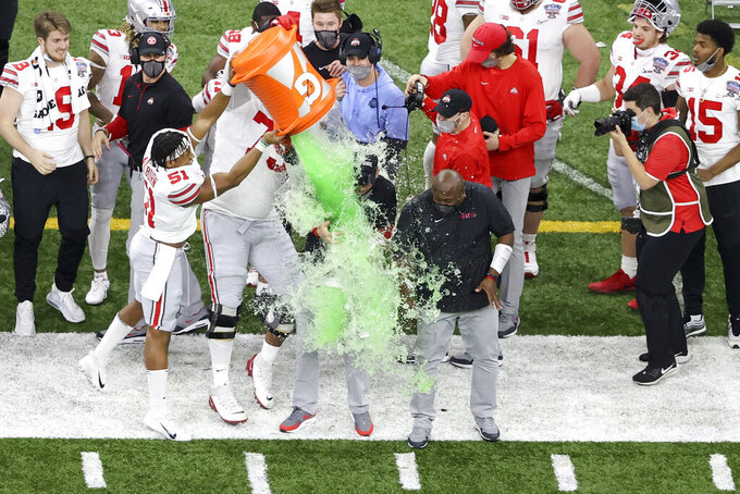 Ohio State coach Ryan Day get soaked in a sports drink of the team's win over Clemson, near the end of the Sugar Bowl NCAA college football game Friday, Jan. 1, 2021, in New Orleans. (AP Photo/Butch Dill)