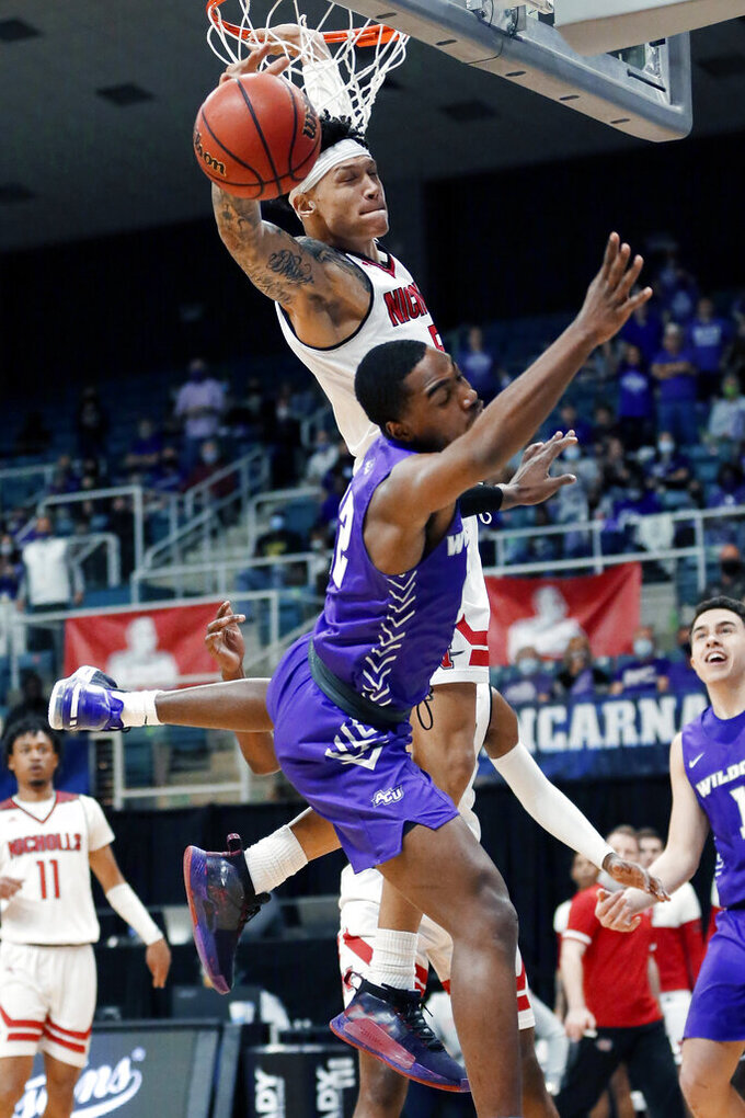 Nicholls State forward Najee Garvin, top, swats down the shot attempt by Abilene Christian guard Mahki Morris, bottom, during the first half of an NCAA college basketball game for the Southland Conference men's tournament championship Saturday, March 13, 2021, in Katy, Texas. (AP Photo/Michael Wyke)