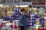 An Indian laborer wearing a mask carries boxes of apples at a wholesale market on the outskirts of Jammu, India, Wednesday, Sept.23, 2020. The nation of 1.3 billion people is expected to become the pandemic's worst-hit country within weeks, surpassing the United States. (AP Photo/Channi Anand)