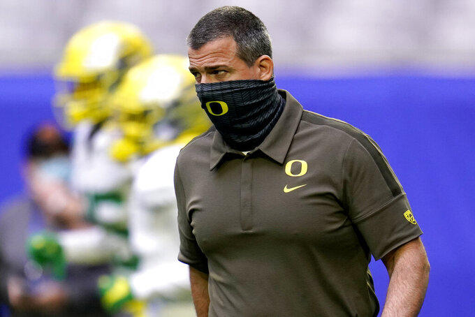 Oregon head coach Mario Cristobal watches his team prior to the Fiesta Bowl NCAA college football game against Iowa State, Saturday, Jan. 2, 2021, in Glendale, Ariz. (AP Photo/Ross D. Franklin)