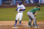 Los Angeles Dodgers' Mookie Betts scores on a single by Corey Seager during the first inning of a baseball game against the Oakland Athletics Tuesday, Sept. 22, 2020, in Los Angeles. Oakland Athletics catcher Sean Murphy is at right. (AP Photo/Ashley Landis)