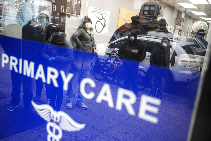 Patients wait inside an urgent care pharmacy while wearing personal protective equipment, Wednesday, March 25, 2020, in the Queens borough of New York. Gov. Andrew Cuomo sounded his most dire warning yet about the coronavirus pandemic Tuesday, saying the infection rate in New York is accelerating and the state could be as close as two weeks away from a crisis that sees 40,000 people in intensive care. Such a surge would overwhelm hospitals, which now have just 3,000 intensive care unit beds statewide. (AP Photo/John Minchillo)