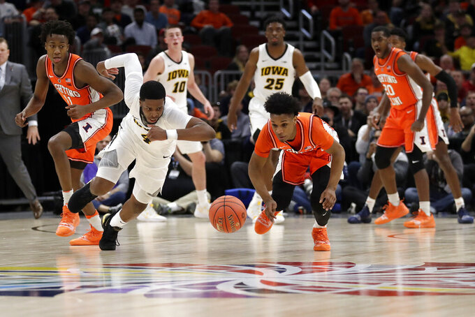 Iowa's Isaiah Moss (4) and Illinois's Trent Frazier chase the loose ball during the first half of an NCAA college basketball game in the second round of the Big Ten Conference tournament, Thursday, March 14, 2019, in Chicago. (AP Photo/Nam Y. Huh)