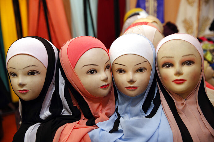 FILE - In this March 30, 2018 file photo, mannequins with veils are on display inside an exhibition hall at the France Muslim Annual Fair in Le Bourget, north of Paris. Islam is the No. 2 religion in a largely Catholic nation where many, especially the anti-immigration far-right, hone to France's roots and view its Muslim population, which grew from the nation's colonial past, as intruders and a threat to the French way of life, including secularism. (AP Photo/Christophe Ena, File)