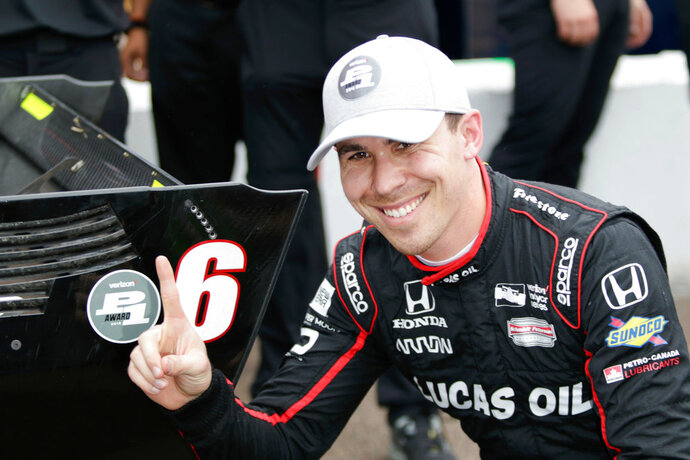 FILE - In this March 10, 2018, file photo, Robert Wickens poses next to his pole-position sticker on his car after taking the pole in qualifying for the in St. Petersburg, Fla. IndyCar auto race. IndyCar newcomer Robert Wickens could have won the first two races of his career _ a surprise to everyone but teammate James Hinchcliffe. (Gabrellia Angotti-Jones/Tampa Bay Times via AP, File)