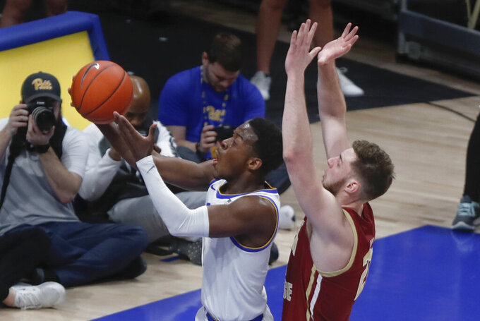 Pittsburgh's Xavier Johnson, left, shoots as Boston College's Nik Popovic defends during the first half of an NCAA college basketball game, Wednesday, Jan. 22, 2020, in Pittsburgh. (AP Photo/Keith Srakocic)