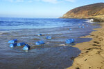 This Saturday, Sept. 14, 2019 photo released by the Ventura County Sheriff's Office shows several barrels of gasloline on the Southern California coast near Malibu. The Ventura County Sheriff's Office says the report came in shortly before dawn Saturday and deputies found a 35-foot panga boat on the shore below Pacific Coast Highway between Malibu and Point Mugu. In addition to 577 pounds of marijuana, investigators found 37 large containers filled with gasoline in the boat, floating in the water and on the beach. (Ventura County Sheriff's Office via AP)
