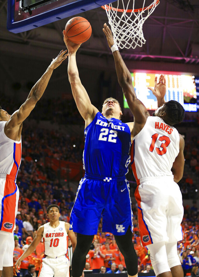 Kentucky forward Reid Travis (22) shoots past Florida center Kevarrius Hayes (13) during the second half of an NCAA college basketball game Saturday, Feb. 2, 2019, in Gainesville, Fla. (AP Photo/Matt Stamey)