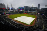 A tarp covers the infield at Truist Park during a rain shower before the scheduled start of a baseball game between the Atlanta Braves and the Miami Marlins on Thursday, Sept. 24, 2020, in Atlanta. (AP Photo/John Bazemore)