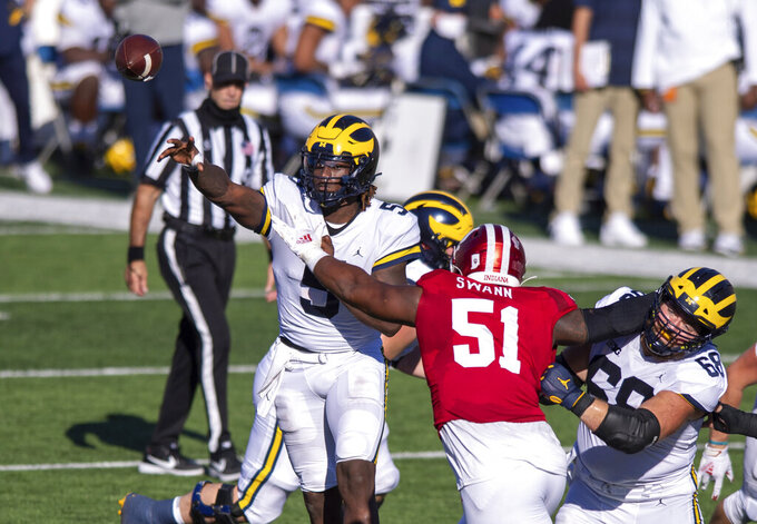 Michigan quarterback Joe Milton (5) gets a pass away as Indiana defensive lineman Jovan Swann (51) closes in on him during the second half of an NCAA college football game Saturday, Nov. 7, 2020, in Bloomington, Ind. Indiana won 38-21. (AP Photo/Doug McSchooler)