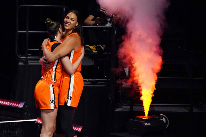 Team WNBA's Dearica Hamby, left, and Liz Cambage embrace before a WNBA All-Star basketball game against the United States, Wednesday, July 14, 2021, in Las Vegas. (AP Photo/John Locher)