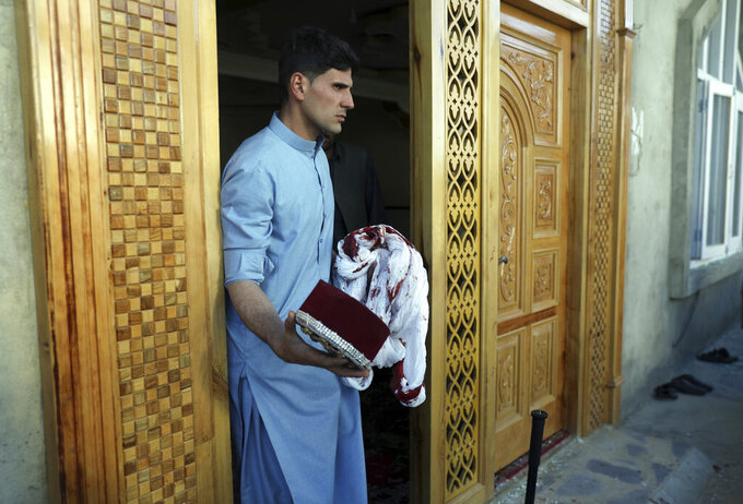 An Afghan man holds a blood-stained turban and cap inside a mosque after a bomb explosion in Shakar Dara district of Kabul, Afghanistan, Friday, May 14, 2021. A bomb ripped through a mosque in northern Kabul during Friday prayers killing 12 worshippers, Afghan police said. (AP Photo/Rahmat Gul)