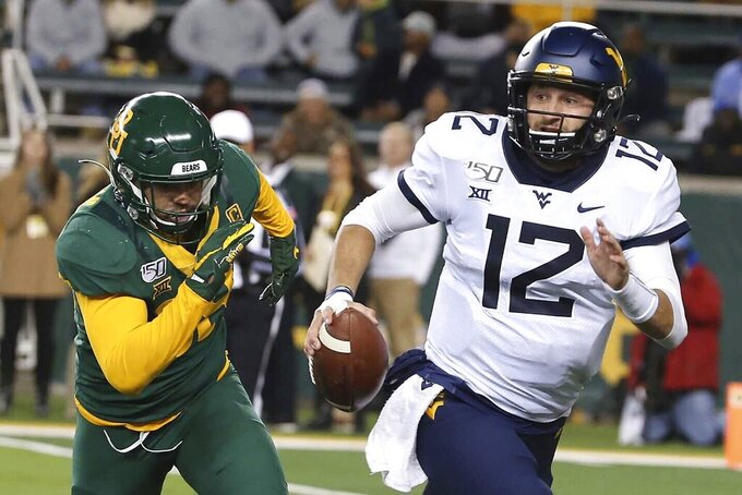 West Virginia quarterback Austin Kendall (12) runs from Baylor linebacker Jordan Williams (38) during the first half of an NCAA college football game in Waco, Texas, Thursday, Oct. 31, 2019. (AP Photo/Jerry Larson)