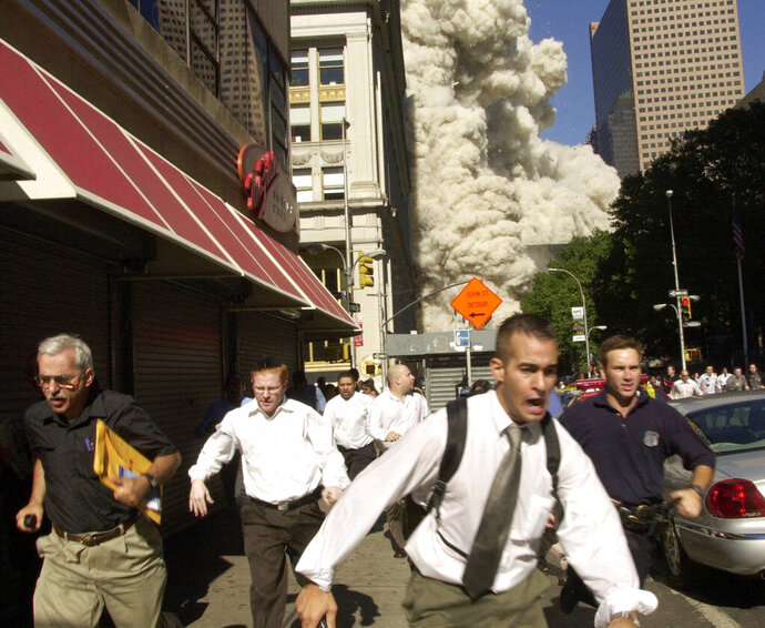 FILE - In this Sept. 11, 2001, file photo, people run from the collapse of one of the twin towers at the World Trade Center in New York. Stephen Cooper, far left, fleeing smoke and debris as the south tower crumbled just a block away on Sept. 11, has died from coronavirus, his family said, according to The Palm Beach Post. (AP Photo/Suzanne Plunkett, File)