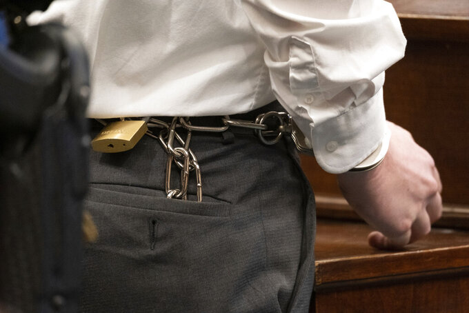 Robert Aaron Long has his hands shackled to his waist as he stands before Judge Ellen McElyea in Superior Court of Cherokee County in Canton, Ga. on Tuesday, July 27, 2021. The man accused of killing eight people, most of them women of Asian descent, at Atlanta-area massage businesses pleaded guilty to four of the murders. He was handed four sentences of life without parole. Robert Aaron Long still faces the death penalty in the four other deaths, which are being prosecuted in a different county. (Ben Gray/Atlanta Journal-Constitution via AP, Pool)