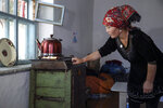 """Gulnar Omirzakh prepares a kettle of tea in her home in Shonzhy, Kazakhstan on Saturday, June 13, 2020. """"God bequeaths children on you. To prevent people from having children is wrong,"""" says Omirzakh of the Chinese government. """"They want to destroy us as a people."""" (AP Photo/Mukhit Toktassyn)"""