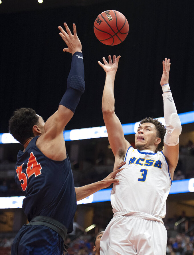 UC Santa Barbara guard JaQuori McLaughlin, right, shoots over Cal State Fullerton forward Jackson Rowe during the first half of an NCAA college basketball game at the Big West men's tournament in Anaheim, Calif., Friday, March 15, 2019. (AP Photo/Kyusung Gong)