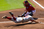 Washington Nationals' Brock Holt, bottom, dives to score as Atlanta Braves catcher Tyler Flowers catches a throw from right field in the second inning of a baseball game, Sunday, Sept. 6, 2020, in Atlanta.(AP Photo/John Amis)