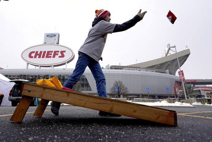 A Kansas City Chiefs fan plays corn hole while tailgating in the parking lot outside Arrowhead Stadium before an NFL football game against the Los Angeles Chargers, Sunday, Jan. 3, 2021, in Kansas City, Mo. (AP Photo/Charlie Riedel)