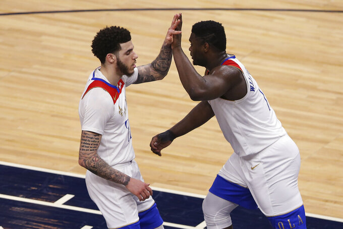 New Orleans Pelicans' Zion Williamson (1) high-fives Lonzo Ball (2) during the first half of the team's NBA basketball game agains the Minnesota Timberwolves on Saturday, May 1, 2021, in Minneapolis. New Orleans won 140-136 in overtime. (AP Photo/Stacy Bengs)