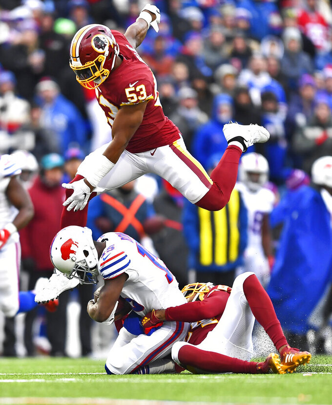 Buffalo Bills wide receiver John Brown (15) is tackled by cornerback Josh Norman (24) as Washington Redskins inside linebacker Jon Bostic (53) jumps over during the second half of an NFL football game, Sunday, Nov. 3, 2019, in Orchard Park, N.Y. (AP Photo/Adrian Kraus)