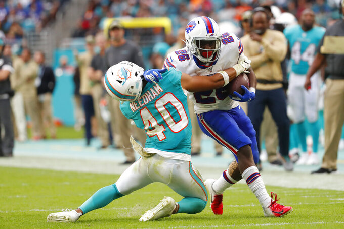 Buffalo Bills running back Devin Singletary (26) blocks a tackle by Miami Dolphins defensive back Nik Needham (40), during the second half at an NFL football game, Sunday, Nov. 17, 2019, in Miami Gardens, Fla. (AP Photo/Wilfredo Lee)