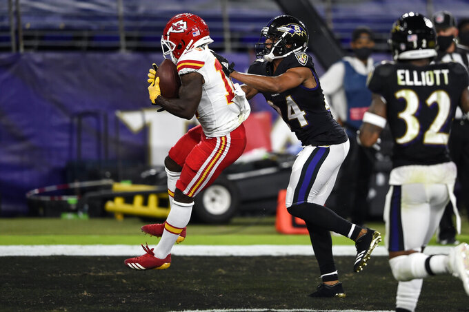 Kansas City Chiefs wide receiver Tyreek Hill (10) catches a pass in front of Baltimore Ravens cornerback Marcus Peters (24) for a touchdown during the first half of an NFL football game Monday, Sept. 28, 2020, in Baltimore. (AP Photo/Gail Burton)