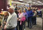 "People wait in line for at an early caucus site at the Sparks Library, Saturday, Feb. 15, 2020 in Sparks, Nev. More than 300 people were waiting in a line that snaked through aisles of book shelves at the library. Dozens left without voting. ""Turnout is much bigger than we expected,"" Sparks site leader Carissa Snedeker said. (AP Photo/Scott Sonner)"