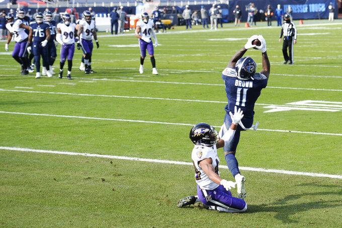 Tennessee Titans wide receiver A.J. Brown (11) catches a touchdown pass as he is defended by Baltimore Ravens cornerback Marlon Humphrey (44) in the first half of an NFL wild-card playoff football game Sunday, Jan. 10, 2021, in Nashville, Tenn. (AP Photo/Mark Zaleski)
