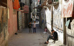 In this April 21, 2019 photo, a Palestinian teenager sits in an alley as children play in front of their family house, in the Shati refugee camp, in Gaza City. The blockade Israel and Egypt imposed on Gaza after the Hamas militant group took power in 2007 has ravaged the economy. The skyrocketing unemployment rates, combined with foreign aid cuts and Hamas' mismanagement, has left thousands of families dependent on food aid and social welfare. Many young Gazans have been forced to put off their dreams of marriage because they cannot afford it. (AP Photo/Adel Hana)