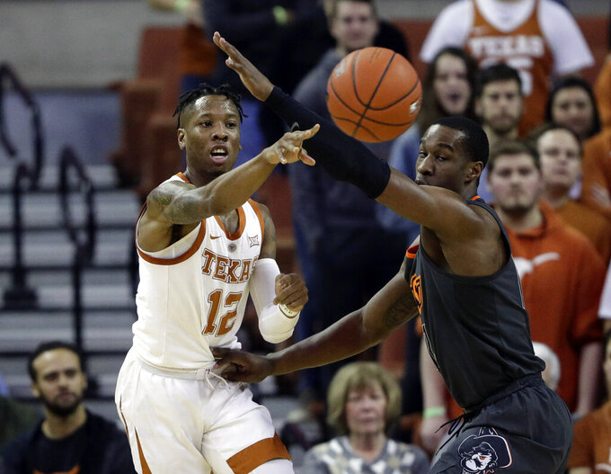 Texas guard Kerwin Roach II, left, passes the ball around Oklahoma State forward Cameron McGriff during the first half of an NCAA college basketball game, Saturday, Feb. 16, 2019, in Austin, Texas. (AP Photo/Eric Gay)