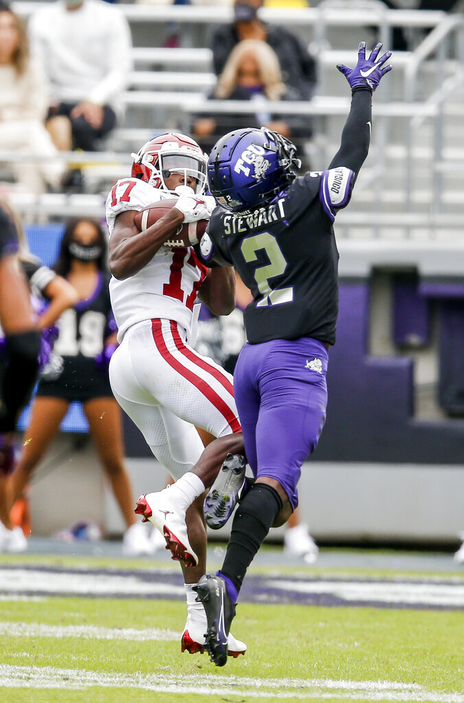 Oklahoma wide receiver Marvin Mims (17) catches a pass as TCU cornerback Kee'yon Stewart (2) defends during the second half of an NCAA college football game, Saturday, Oct. 24, 2020, in Fort Worth, Texas. Mims would run the pass in for a touchdown on the play.  (AP Photo/Brandon Wade)