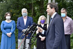 U.S. Rep. Seth Moulton, D-Mass., second from left, speaks to reporters as, from left Alma and Brian Hart, parents of U.S. Army Pfc. John Hart, who was killed in 2003, and Laurie and Joe Desiato, parents of U.S. Marine Lance Cpl. Travis Desiato, who was killed in 2004, listen during a news conference Thursday, Sept. 10, 2020, in Bedford, Mass. The two families of servicemen from Bedford, Mass., addressed reports of President Trump's remarks about military service by the bridge named as a memorial to their sons. (AP Photo/Josh Reynolds)