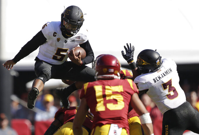 Arizona State quarterback Manny Wilkins, top left, leaps over Southern California linebacker Levi Jones, bottom left, during the first half of an NCAA college football game Saturday, Oct. 27, 2018, in Los Angeles. (AP Photo/Marcio Jose Sanchez)