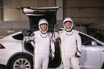 In this Friday, Jan. 17, 2020 photo made available by NASA, astronauts Doug Hurley, left, and Robert Behnken pose in front of a Tesla Model X car during a SpaceX launch dress rehearsal at Kennedy Space Center in Cape Canaveral, Fla. The NASA astronauts rode to the pad in the electric vehicle made by Elon Musk's company. (Kim Shiflett/NASA via AP)