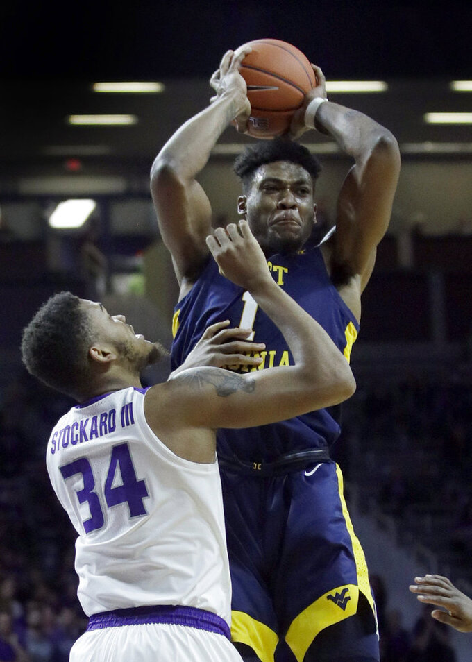 West Virginia forward Derek Culver (1) passes to a teammate while covered by Kansas State forward Levi Stockard III (34) during the first half of an NCAA college basketball game in Manhattan, Kan., Wednesday, Jan. 9, 2019. (AP Photo/Orlin Wagner)