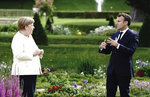 French President Emmanuel Macron gestures as he talks to German Chancellor Angela Merkel during a meeting at Meseberg Castle, the German government's guest house in Meseberg, Germany, June 29, 2020. One of the topics of the meeting is the European reconstruction plan of 750 billion euros in the Corona crisis. (Kay Nietfeld/dpa via AP)