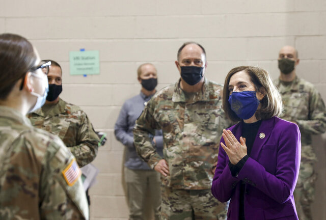 Oregon Gov. Kate Brown visits with National Guard members at the Marion County and Salem Health COVID-19 vaccination clinic on Wednesday, Jan. 13, 2021 at the Oregon State Fairgrounds in Salem, Ore.(Abigail Dollins/Statesman-Journal via AP, Pool)