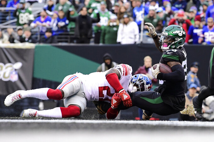 New York Jets running back Le'Veon Bell, right, rushes past New York Giants' Jabrill Peppers (21) for a touchdown during the second half of an NFL football game Sunday, Nov. 10, 2019, in East Rutherford, N.J. (AP Photo/Steven Ryan)
