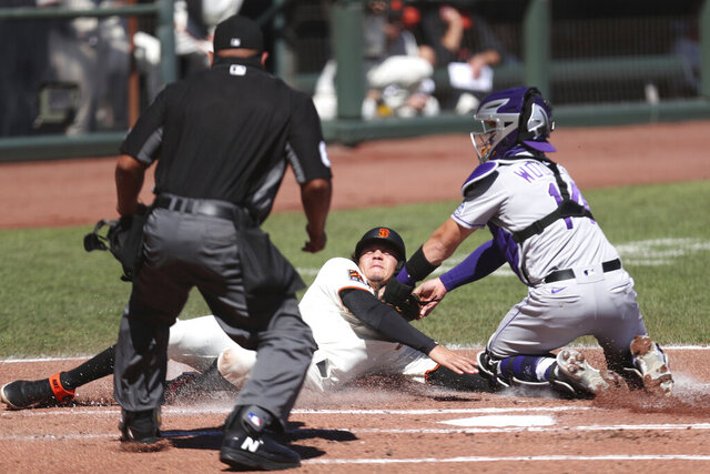 San Francisco Giants' Wilmer Flores is tagged out at home by Colorado Rockies' Tony Wolters during the second inning of a baseball game in San Francisco, Thursday, Sept. 24, 2020. (AP Photo/Jed Jacobsohn)