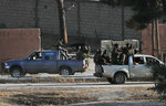 In this photo taken from the Turkish side of the border between Turkey and Syria, in Akcakale, Sanliurfa province, southeastern Turkey, Turkish-backed Syrian opposition fighters on pick-up trucks celebrate as they drive in Tal Abyad, Syria, Sunday, Oct. 13, 2019. State-run Anadolu news agency reported Tal Abyad had fallen to a Turkish military offensive on Sunday. Even after the announcement, sporadic gunfire and the occasional mortar round could still be heard in the town, which is on the border with Turkey, while smoke could be seen rising from several points in the town. (AP Photo/Cavit Ozgul)