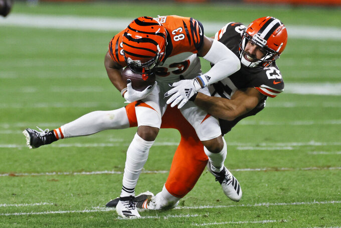Cleveland Browns strong safety Andrew Sendejo (23) tackles Cincinnati Bengals wide receiver Tyler Boyd (83) after a pass reception during the second half of an NFL football game Thursday, Sept. 17, 2020, in Cleveland. (AP Photo/Ron Schwane)