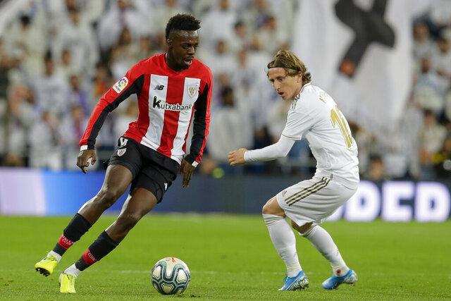 Athletic Bilbao's Inaki Williams, left, and Real Madrid's Luka Modric fight for the ball during a Spanish La Liga soccer match between Real Madrid and Athletic Bilbao at the Santiago Bernabeu stadium in Madrid, Spain, Sunday Dec. 22, 2019. (AP Photo/Paul White)