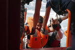 A man is helped onto the Ocean Viking after being rescued from a small and overcrowded wooden boat some 53 nautical miles (98 kilometers) from the coast of Libya in the Mediterranean Sea, Tuesday, Sept. 17, 2019. The humanitarian rescue ship pulled 48 people from the boat including a newborn and a pregnant woman. (AP Photo/Renata Brito)