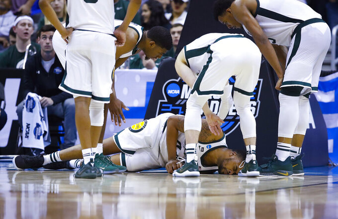 Michigan State forward Nick Ward lies on the ground surrounded by his teammates after injuring his hand during the second half against LSU in a semifinal in the NCAA men's college basketball tournament East Region in Washington, Friday, March 29, 2019. (AP Photo/Alex Brandon)