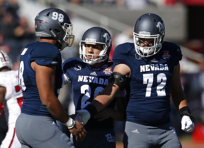 Nevada place kicker Ramiz Ahmed (26) celebrates with Sam Hammond (98) and Miles Beach (72) after kicking a field goal in the first half of the Arizona Bowl NCAA college football game against Arkansas State, Saturday, Dec. 29, 2018, in Tucson, Ariz. (AP Photo/Rick Scuteri)